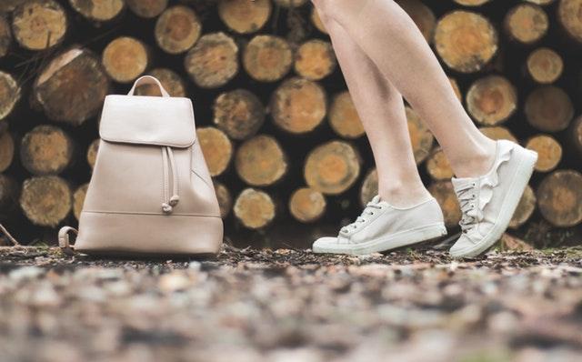 Ženské nohy pred naskladaným drevom , v teniskách.jpg