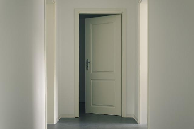 Pootvorené biele dvere, stena