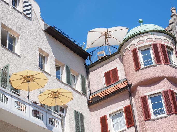 Budova, balkóny, dáždniky proti slnku