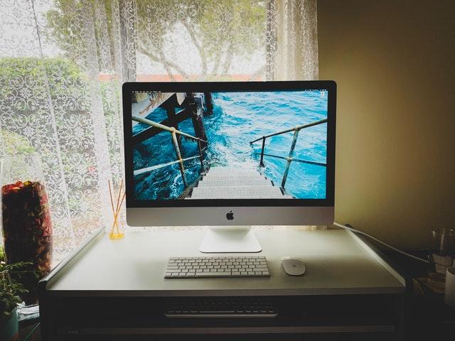 Počítač, ktorý má na pozadí more, položený na stole pod oknom.jpg