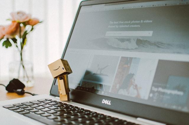 Počítač, na ktorom je položená kartónová postavička hľadiaca na monitor.jpg