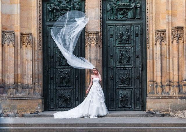 Žena v dlhých bielych svadobných šatách vychádza z kostola a vo vzduchu jej veje závoj.jpg