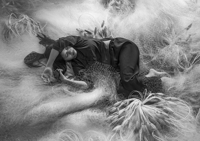 Žena v čiernej pyžame spí v spleti rybárskych sietí.jpg