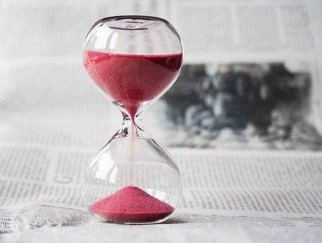 Sklenené presýpacie hodiny s červeným pieskom na novinovom papieri.jpg