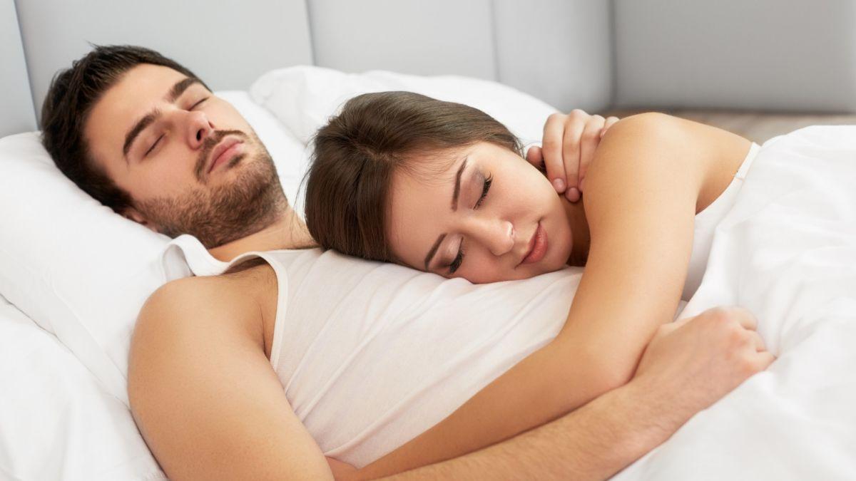 woman_sleeping_while_holding_alarm_clock